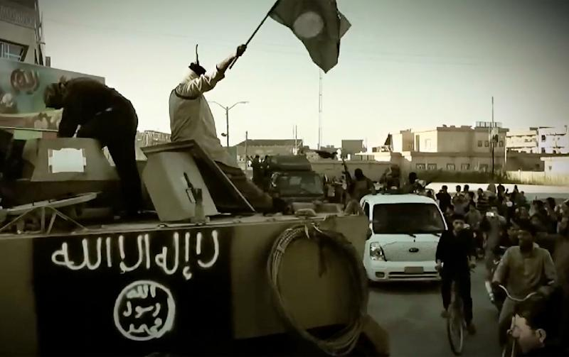 An image grab taken from a propaganda video released on March 17, 2014 by the Islamic State shows jihadist fighters standing on an armoured vehicle in the Iraqi province of Anbar (AFP Photo/-)