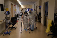 FILE - In this Dec. 22, 2020 file photo Physical therapist Alireza Akbarpour, right, helps Maria Herrera exercise in a COVID-19 unit at Providence Holy Cross Medical Center in the Mission Hills section of Los Angeles. California became the first state to record 2 million confirmed coronavirus cases, reaching the milestone on Christmas Eve as close to the entire state was under a strict stay-at-home order and hospitals were flooded with the largest crush of cases since the pandemic began. (AP Photo/Jae C. Hong,File)