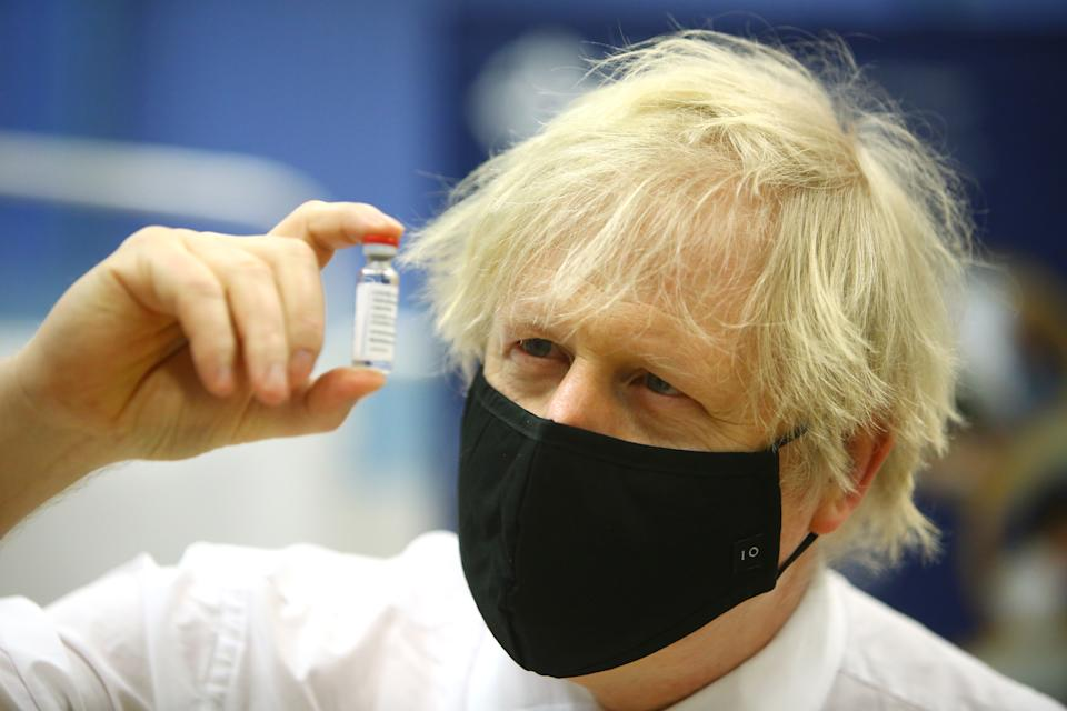 "CWMBRAN, WALES – FEBRUARY 17: British Prime Minister Boris Johnson poses with a vial of the Oxford/AstraZeneca vaccine during a visit to the vaccination centre at Cwmbran Stadium on February 17, 2021 in Cwmbran, Wales. The Prime Minister visited the vaccination centre to see the progress of the COVID-19 vaccine roll out in Wales. During the visit he explained that the lifting of the coronavirus lockdown would be ""based firmly on a cautious and prudent approach"". (Photo by Geoff Caddick – WPA Pool/Getty Images)"