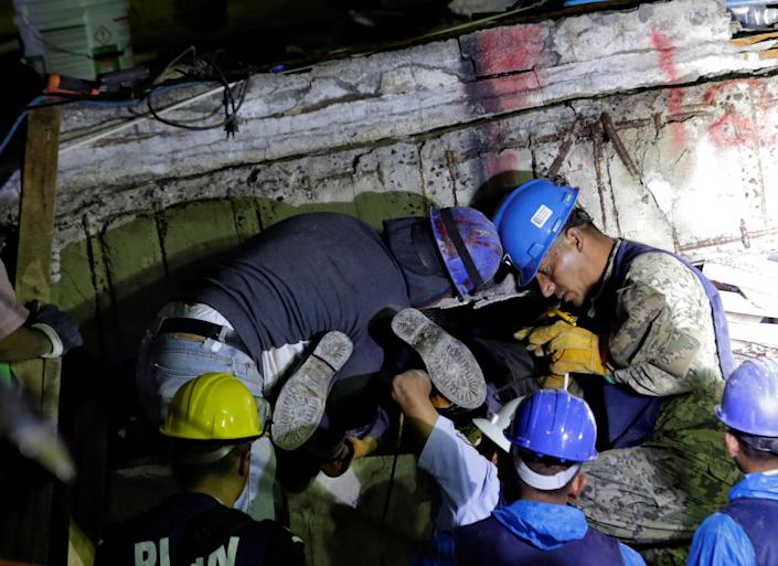 <p>Members of a rescue team hold a fellow rescuer from the Topos volunteer search and rescue group by his feet during the search for students at the Enrique Rebsamen school after an earthquake in Mexico City, Mexico, Sept. 21, 2017. (Photo: Daniel Becerril/Reuters) </p>