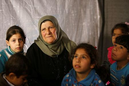 Amira Gharmoush sits with her grandchildren inside a tent in Herjelleh shelter in Damascus countryside, Syria March 30, 2018. REUTERS/Omar Sanadiki