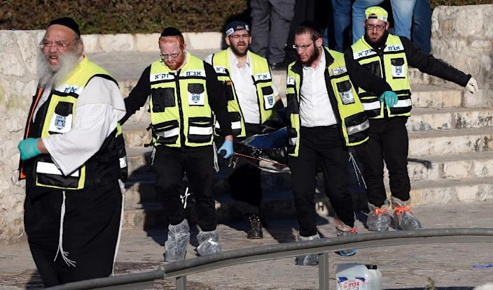 Ultra-Orthodox Jewish ZAKA volunteers carry the body of a Palestinian assailant following an attack at Damascus Gate, a main entrance to Jerusalem's Old City, on February 3, 2016 (AFP Photo/Ahmad Gharabli)