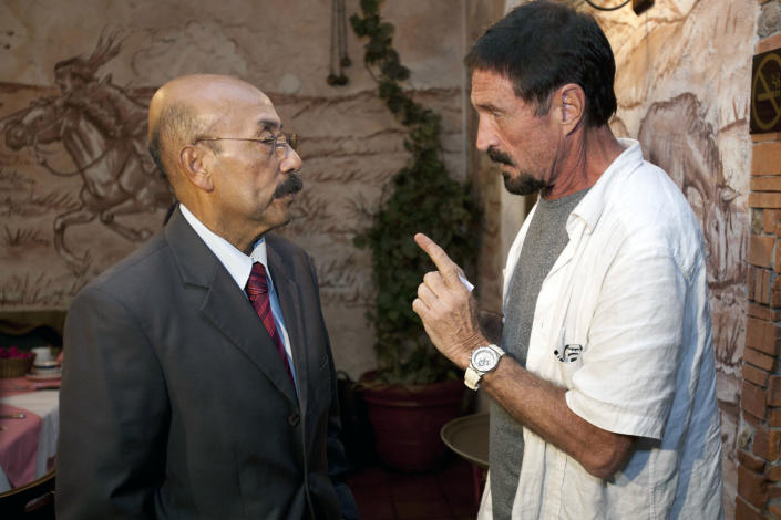 """Software company founder John McAfee talks to his lawyer Telesforo Guerra, right, after giving an interview at a local restaurant in Guatemala City, Tuesday, Dec. 4, 2012. McAfee, 67, has been identified as a """"person of interest"""" in the killing of his neighbor in Belize, 52-year-old Gregory Faull. Police are urging McAffe to come in for questioning. The anti-virus company founder fled Belize and is seeking political asylum in Guatemala, according to Guerra. (AP Photo/Moises Castillo)"""