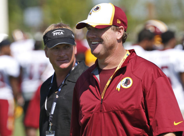 FILE - In this July 25, 2014, file photo, ESPN broadcaster and former NFL coach Jon Gruden, left, walks with his brother, Washington Redskins head coach Jay Gruden, after practice at the team's NFL football training facility in Richmond, Va. With Jon leaving Monday Night Football to return to the sideline after a decade away, and Jay entering his fifth season, they will join the Harbaughs as the only sets of siblings to simultaneously hold jobs as NFL head coaches. (AP Photo, File)