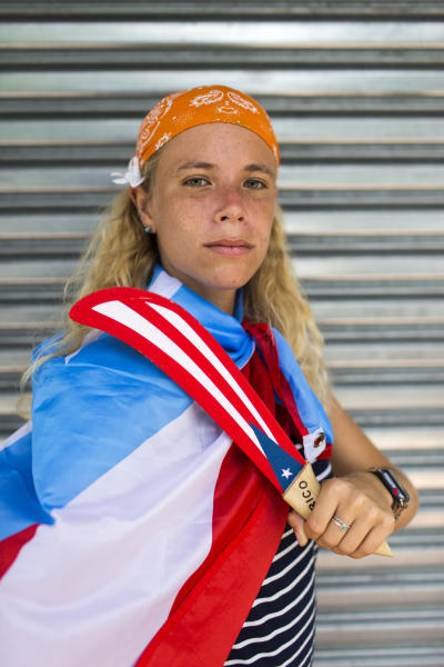 In this July 25, 2019 photo Paula Martinez poses for a portrait as people gather to celebrate the resignation of Gov. Ricardo Rossello after weeks of protests over leaked obscene, misogynistic online chats, in San Juan, Puerto Rico. The historic achievement was born out of a leaderless movement that relied heavily on social media, the appearance of music stars including Ricky Martin, Residente and Bad Bunny and an angry populace fed up with corruption. (AP Photo/Dennis M. Rivera Pichardo)