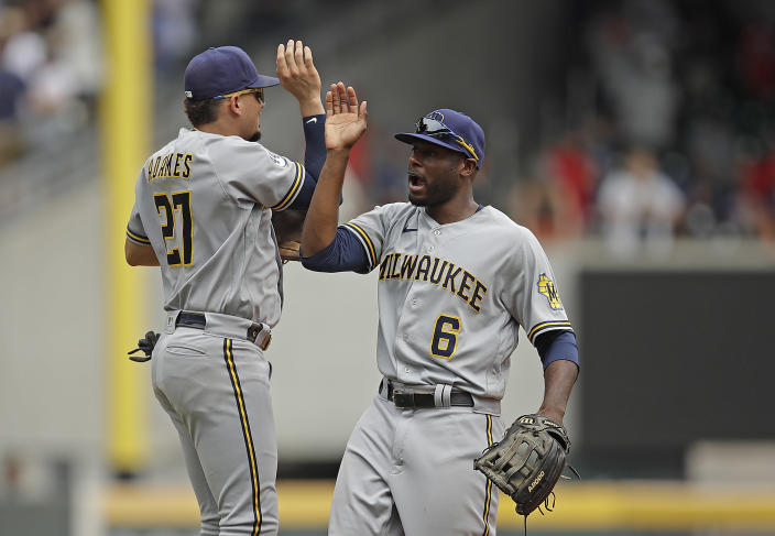 Milwaukee Brewers' Willy Adames, left, celebrates with Lorenzo Cain (6) at the end of a baseball game against the Atlanta Braves, Sunday, Aug. 1, 2021, in Atlanta. (AP Photo/Ben Margot)