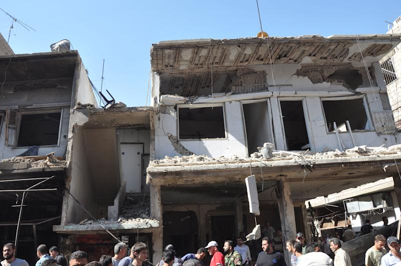 In this photo released by the Syrian official news agency SANA, Syrian citizens gather under damaged houses after a car bomb exploded in the suburb of Jaramana, Damascus, Syria, Thursday, July 25, 2013. Syria's state-run news agency says many people have been killed and scores wounded in a powerful car bomb explosion near Damascus. (AP Photo/SANA)