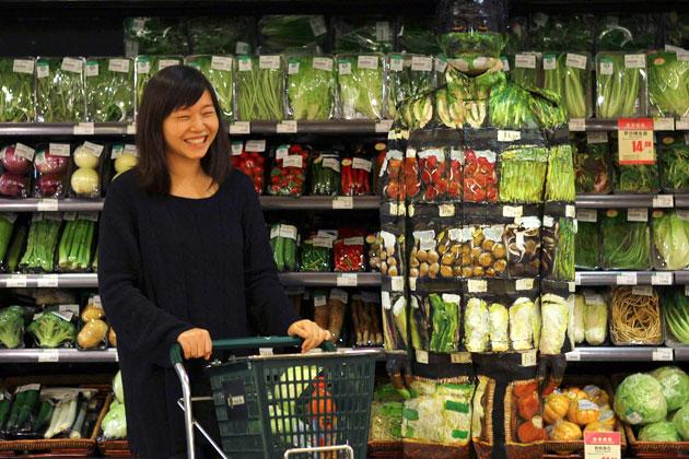 A woman laughes as she pushes a trolley past artist Liu Bolin during his demonstration to blend in with the vegetables on the shelves at a supermarket in Beijing, November 10, 2011. Liu, also known as the 'Vanishing Artist', started his optical illusion artworks of becoming 'invisible' more than six years ago. Picture taken November 10, 2011. REUTERS/China Daily (CHINA - Tags: SOCIETY TPX IMAGES OF THE DAY) CHINA OUT. NO COM