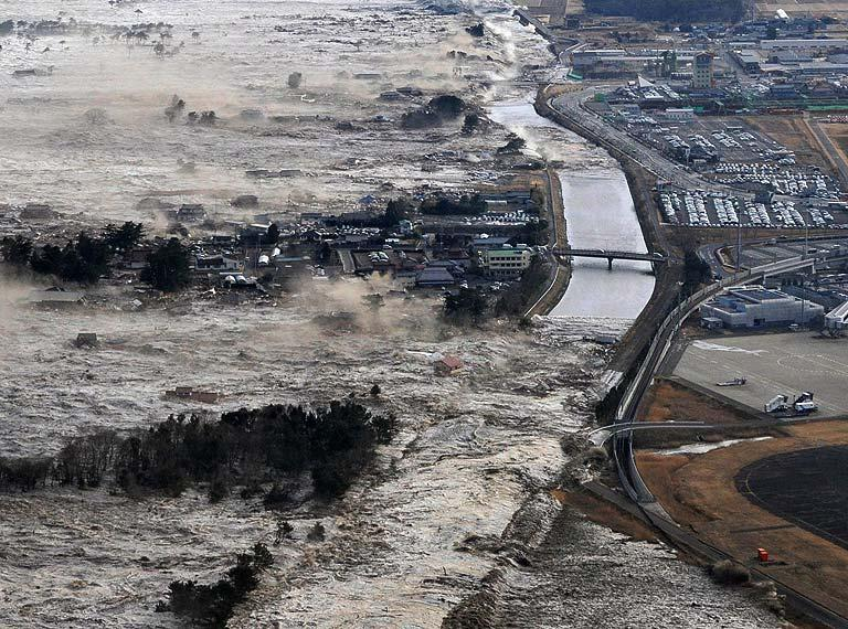 Earthquake-triggered tsumanis sweep shores along Iwanuma in northern Japan on Friday March 11, 2022. The magnitude 8.9 earthquake slammed Japan's eastern coast Friday, unleashing a 13-foot (4-meter) tsunami that swept boats, cars, buildings and tons of debris miles inland. (AP Photo/Kyodo News)