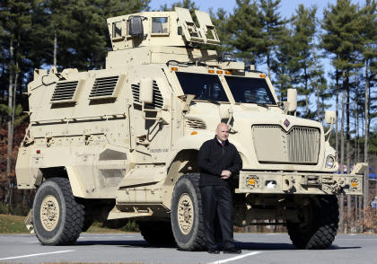 Warren County Undersheriff Shawn Lamouree poses in front the department's mine resistant ambush protected vehicle, or MRAP, on Wednesday, Nov. 13, 2013, in Queensbury, N.Y. The hulking vehicles, built for about $500,000 each at the height of the war, are among the biggest pieces of equipment that the Defense Department is giving to law enforcement agencies under a national military surplus program. (AP Photo/Mike Groll)