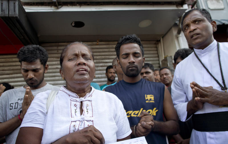 People pray during a nationwide three-minutes silence as a tribute to Easter Sunday attack victims in Colombo, Sri Lanka, Tuesday, April 23, 2019. Easter Sunday bombings of churches, luxury hotels and other sites was Sri Lanka's deadliest violence since a devastating civil war in the South Asian island nation ended a decade ago. (AP Photo/Gemunu Amarasinghe)