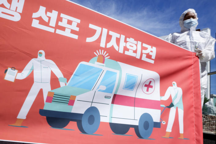 A member of a hospital labor union holds a banner during a press conference demanding for measures to expand manpower at the hospitals and improve their working conditions in Seoul, South Korea, Thursday, Sept. 16, 2021. (AP Photo/Lee Jin-man)