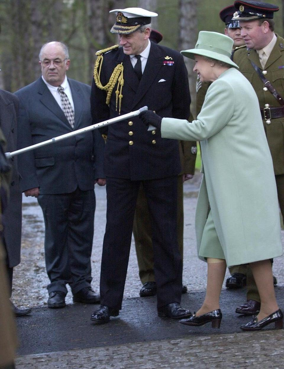 The Queen gestures with her stick in 2003 (PA) (PA Archive)