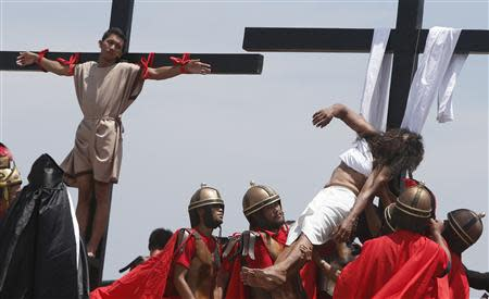 Penitent Ruben Enaje (R), in his 28th year of crucifixion, is lowered from a wooden cross after re-enacting the death of Jesus Christ on Good Friday in San Fernando, Pampanga in northern Philippines April 18, 2014. REUTERS/Erik De Castro