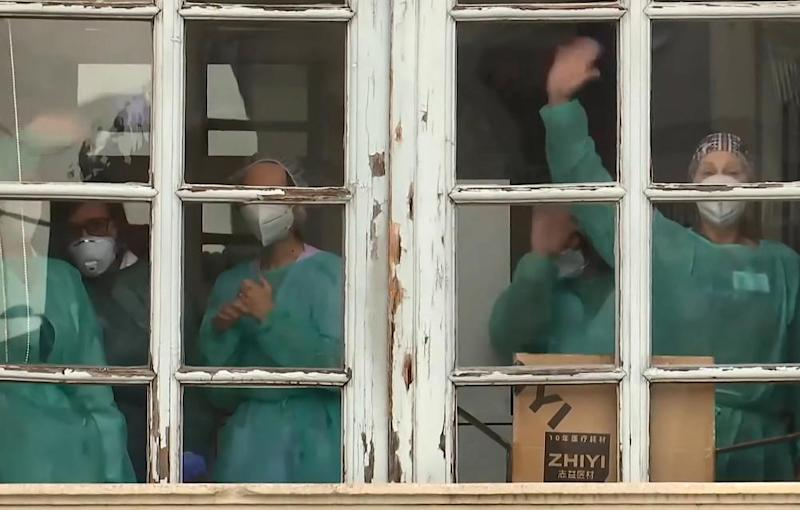 Staff at a retirement home in Bergamo, Italy, wave to radiological, chemical and biological defence experts from the Russian Defence Ministry who had come to carrying out a full disinfection.