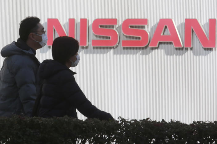 """FILE - In this Feb. 9, 2021, file photo, people walk past the corporate logo at Nissan Motor Co.'s global headquarters in Yokohama, near Tokyo. Former Nissan Chief Executive Hiroto Saikawa told a Japanese court Wednesday, Feb. 24, 2021, he believed the compensation for his predecessor Carlos Ghosn was too low """"by international standards,"""" and so he supported Ghosn's retirement packages to prevent him from leaving. (AP Photo/Koji Sasahara, File)"""