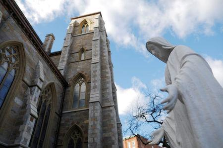 A statue of the Virgin Mary stands next to the Cathedral of the Holy Cross, where Cardinal Bernard Law, the former Archbishop of Boston who resigned in 2002 in disgrace after covering up years of sexual abuse of children, served in Boston, Massachusetts, U.S., December 20, 2017.   REUTERS/Brian Snyder