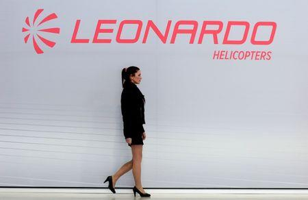 A hostess walks past a Leonardo's helicopters logo at the headquarters in Vergiate