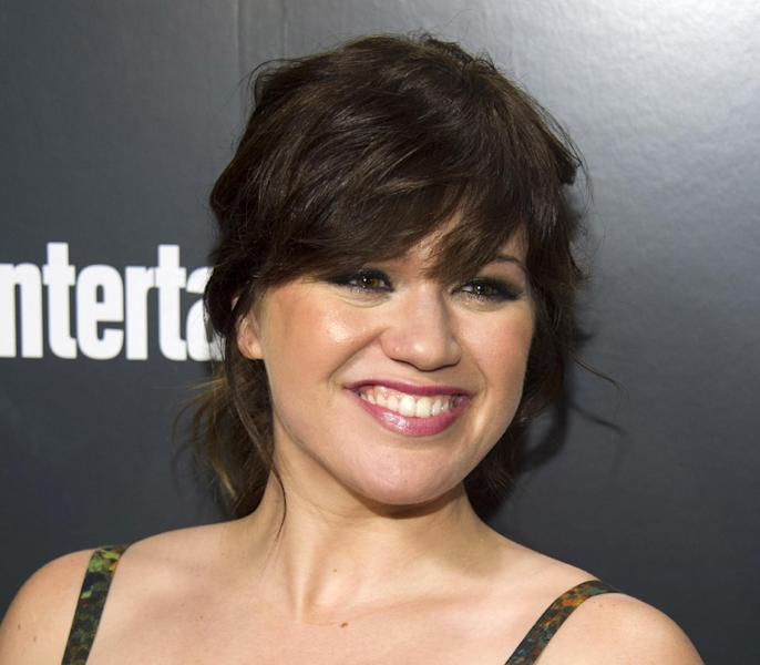 """FILE - This May 15, 2012 file photo shows Kelly Clarkson attending the Entertainment Weekly and ABC Upfronts Party in New York. The Obama inauguration committee planning the Jan. 21 event announced Wednesday that Clarkson will perform """"My Country `Tis of Thee"""" and James Taylor will sing """"America the Beautiful"""" at the swearing-in ceremony on the Capitol's west front. Beyonce will sing the national anthem at President Barack Obama's inauguration ceremony. (AP Photo/Charles Sykes File)"""