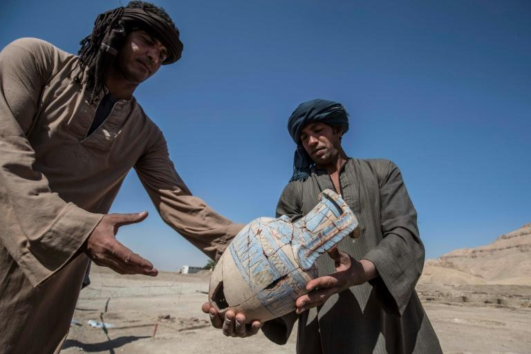 At the site near Luxor, home of the legendary Valley of the Kings, workers carefully carried ancient pots and showed human and animal remains dug up from the earth as members of the media toured around curved brick walls and rudimentary streets