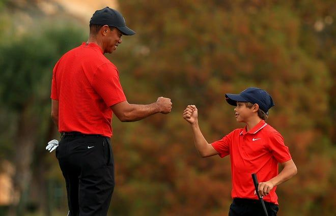 Tiger Woods of the United States and son Charlie Woods fist bump on the 18th hole during the final round of the PNC Championship at the Ritz Carlton Golf Club on Dec. 20, 2020 in Orlando, Fla.