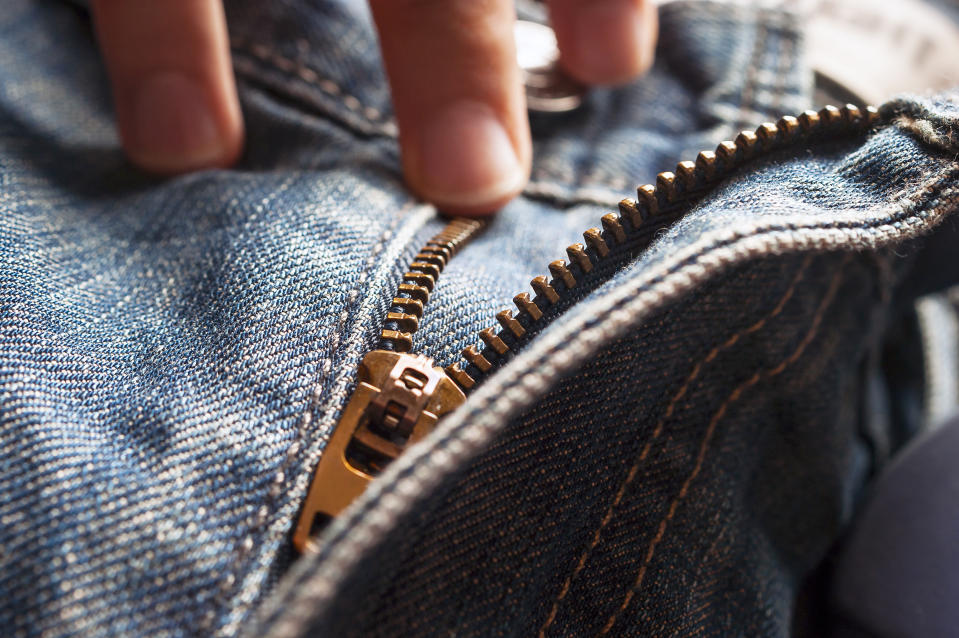 Fingers on Button and Elements of Denim Blue Jeans Metal Zipper.