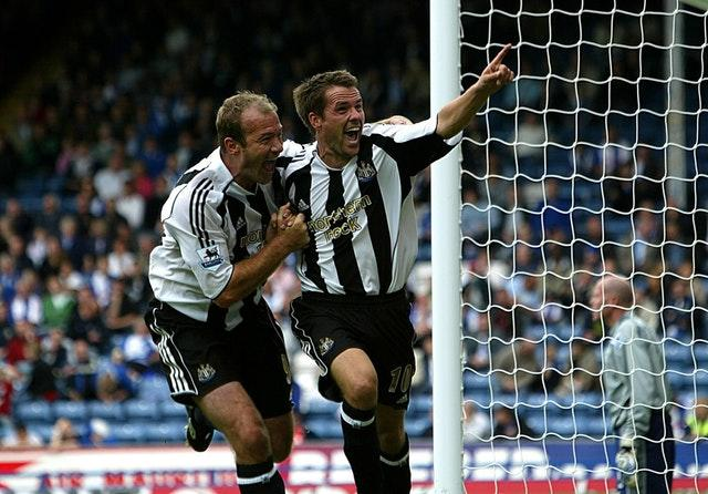 Michael Owen celebrates with Alan Shearer after scoring his first goal for the club against Blackburn
