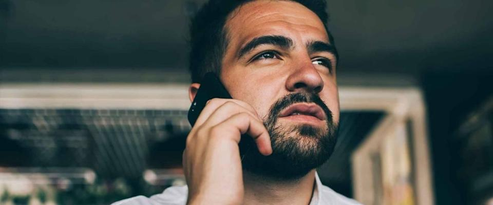 Pensive caucasian male in white shirt concentrated during mobile phone conversation looking up, bearded confident businessman making smartphone call during coffee break in cafe interior