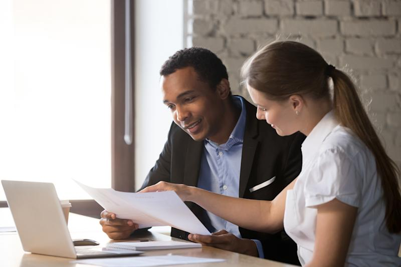 Female financial advisor insurer banker consulting male african american client about contract, caucasian mentor hr and black intern new employee discussing documents at meeting advice