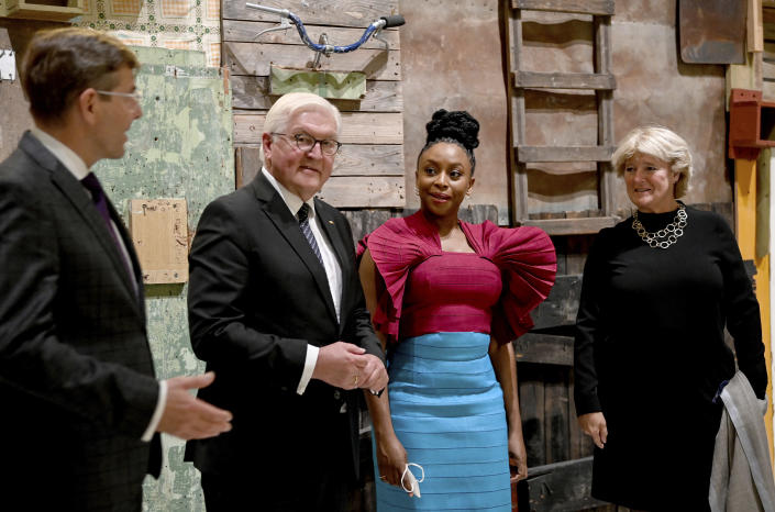 Germany's President Frank-Walter Steinmeier, center left, writer Chimamanda Ngozi Adichie, center right, and Monika Grutters, Minister of State for Culture, are guided through the exhibition by Hartmut Dorgerloh, General Director and Chairman of the Board of the Humboldt Forum Foundation, left, in the Berlin Palace, Berlin, Germany, Wednesday Sept. 22, 2021, during the ceremony marking the exhibition opening of the Ethnological Museum, the Museum of Asian Art of the National Museums in Berlin/Prussian Cultural Heritage Foundation and the Humboldt Forum Foundation. (Britta Pedersen/Pool via AP)