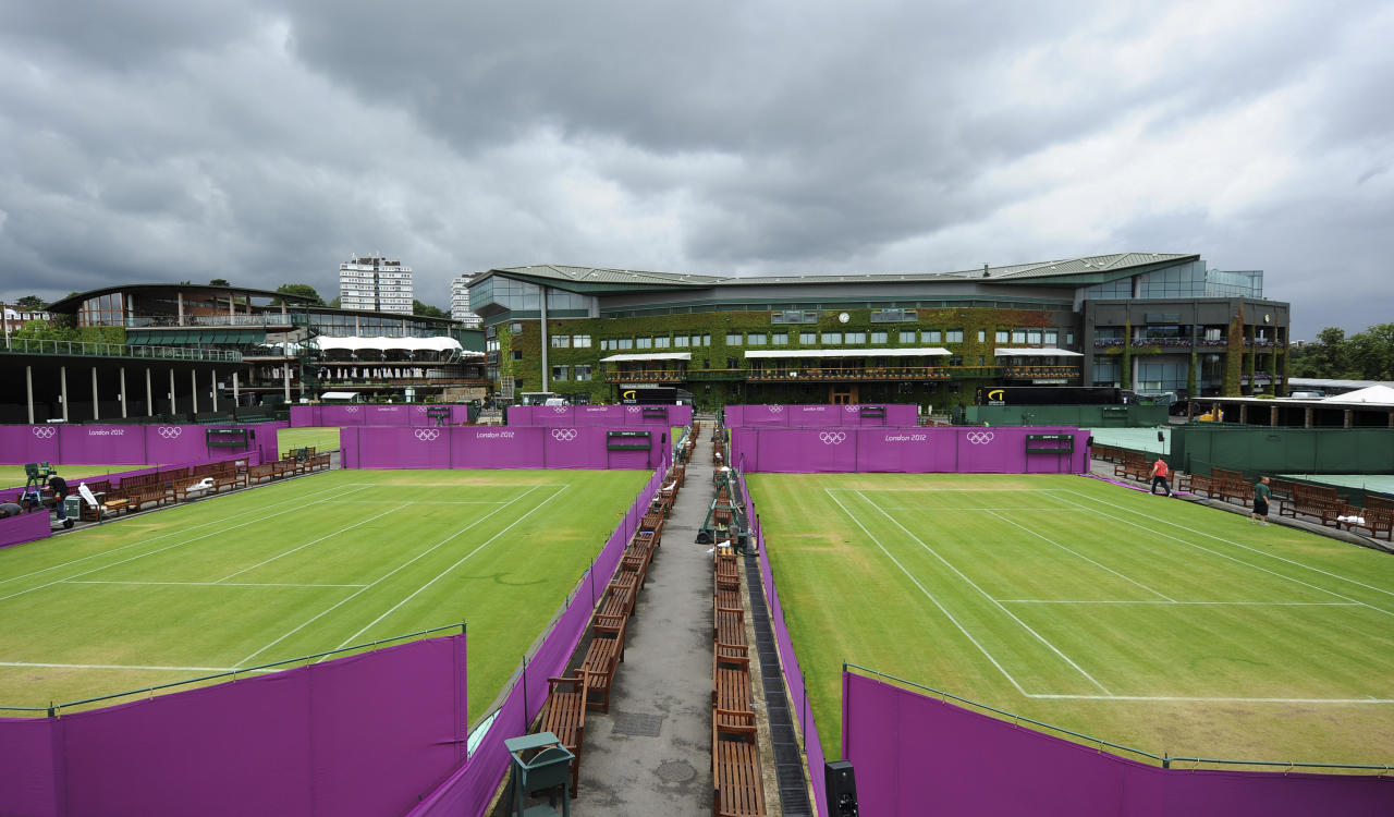 Outside courts are surrounded with Olympic hoarding at the All England Lawn Tennis Club (AELTC) as preparations are made for the London 2012 Olympic Games, in London July 9, 2012.    REUTERS/Ki Price     (BRITAIN - Tags: SPORT OLYMPICS TENNIS)
