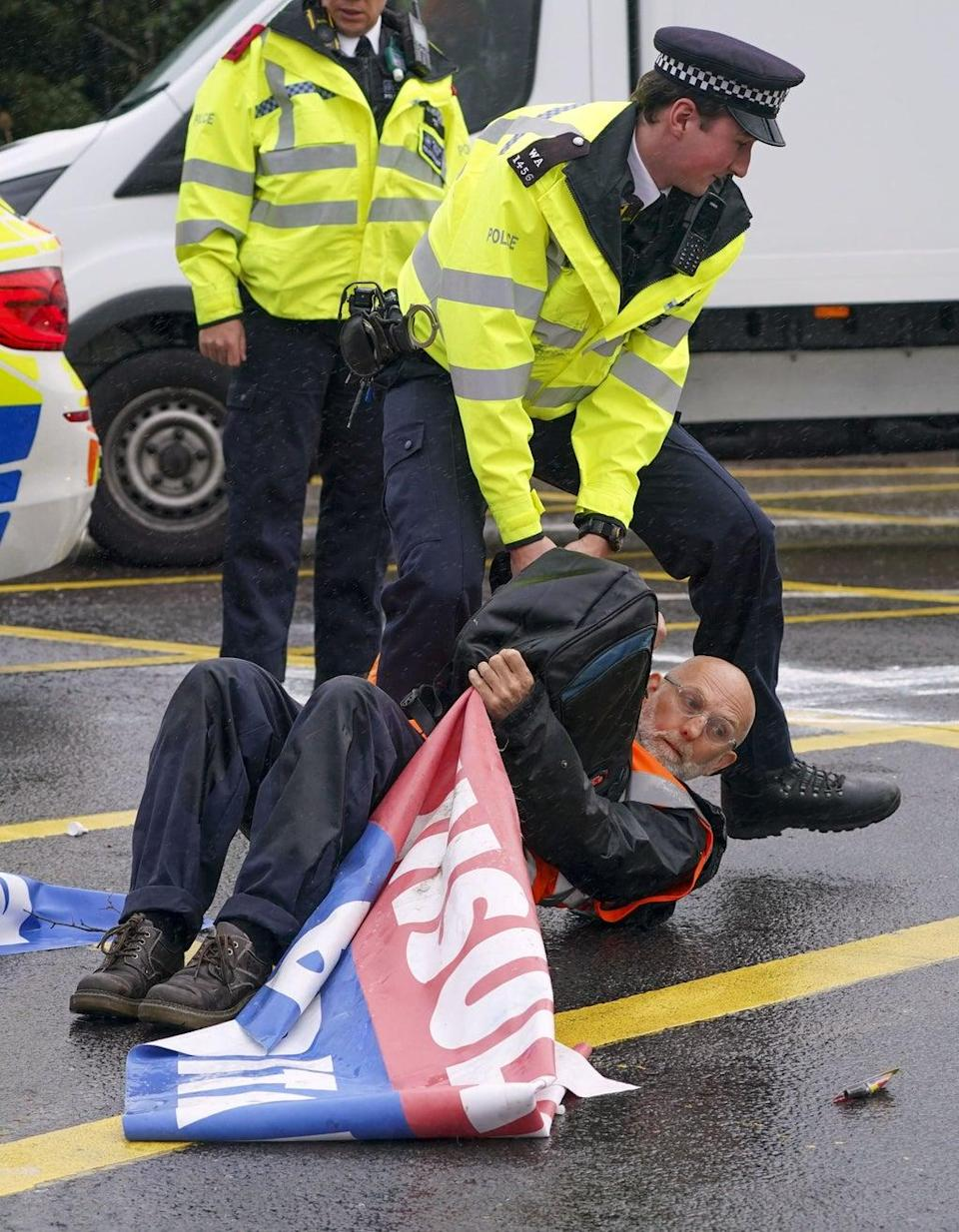 Police officers detain a protester from Insulate Britain occupying a roundabout leading from the M25 motorway to Heathrow (Steve Parsons/PA) (PA Wire)