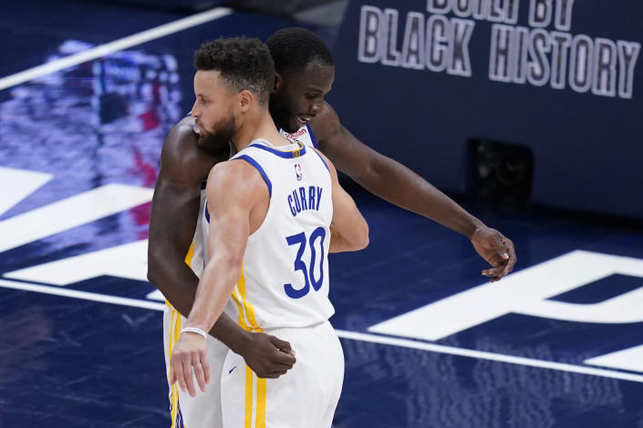 Golden State Warriors' Draymond Green and Stephen Curry embrace following the team's NBA basketball game against the Indiana Pacers, Wednesday, Feb. 24, 2021, in Indianapolis. (AP Photo/Darron Cummings)