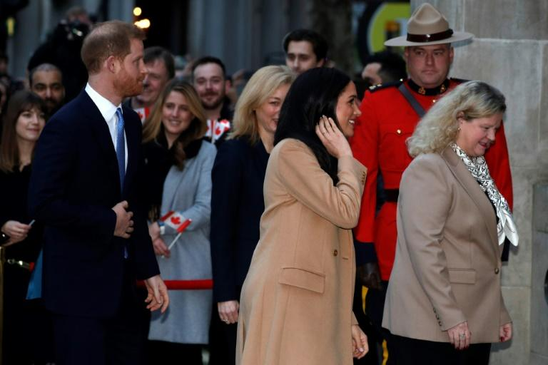 Britain's Prince Harry, Duke of Sussex (L) and Meghan, Duchess of Sussex (C) gesture on their arrival for a visit to Canada House in thanks for the warm Canadian hospitality and support they received during their recent stay in Canada, in London on January 7, 2020