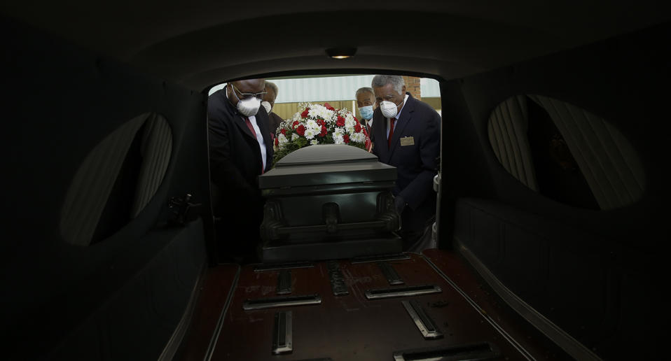 Funeral parlour workers load a coffin into a hearse.