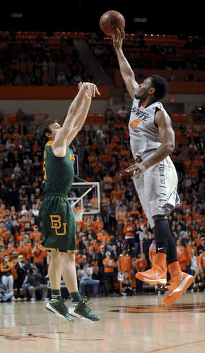 Oklahoma State forward Brian Williams, right, blocks the shot of Baylor guard Brady Heslip during the first half of an NCAA college basketball game in Stillwater, Okla., Saturday, Feb. 1, 2014. Baylor won 76-70. (AP Photo/Brody Schmidt)