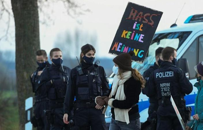A woman with a placard reading 'hate is no opinion' walks past police officers during an anti-AfD demonstration