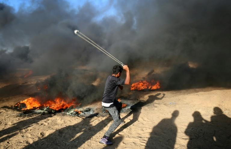 A Palestinian protester uses a slingshot next to burning tyres during a demonstration in Gaza along the border with Israel on August 10, 2018