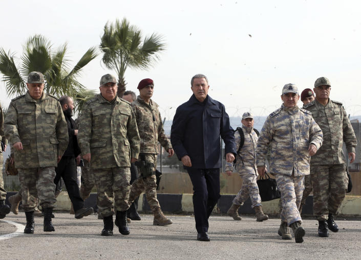 Turkey's National Defence Minister Hulusi Akar, center, and Turkish army's top commanders arrive to inspect troops at the border with Syria, in Hatay, Turkey, Monday, Feb. 3, 2020. Turkey hit targets in northern Syria, responding to shelling by Syrian government forces that killed at least eight Turkish military personnel, Turkish President Recep Tayyip Erdogan said Monday. A Syrian war monitor said 13 Syrian troops were also killed.(Turkish Defence Ministry via AP, Pool)