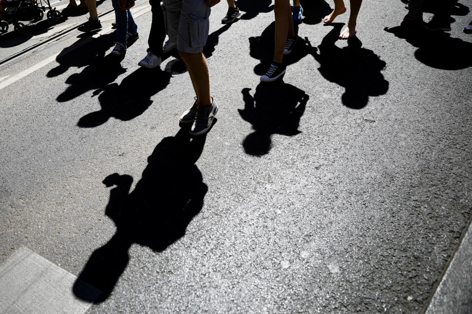 Protestors cast there shadow on the street as they attend a demonstration with the slogan 'The end of the pandemic - freedom day' - against coronavirus restrictions in Berlin, Germany, Saturday, Aug. 1, 2020. It comes amid increasing concern about an upturn in infections in Germany. (AP Photo/Markus Schreiber)