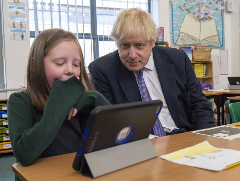 Britain's Prime Minister Boris Johnson, right, reacts with pupils during a visit to Middleton Primary School in Milton Keynes, England, Friday Oct. 25, 2019. European Union ambassadors agreed Friday that the bloc should grant Britain's request for another extension to the Brexit deadline but have not yet figured out how long that delay should be. (Paul Grover/Pool via AP)