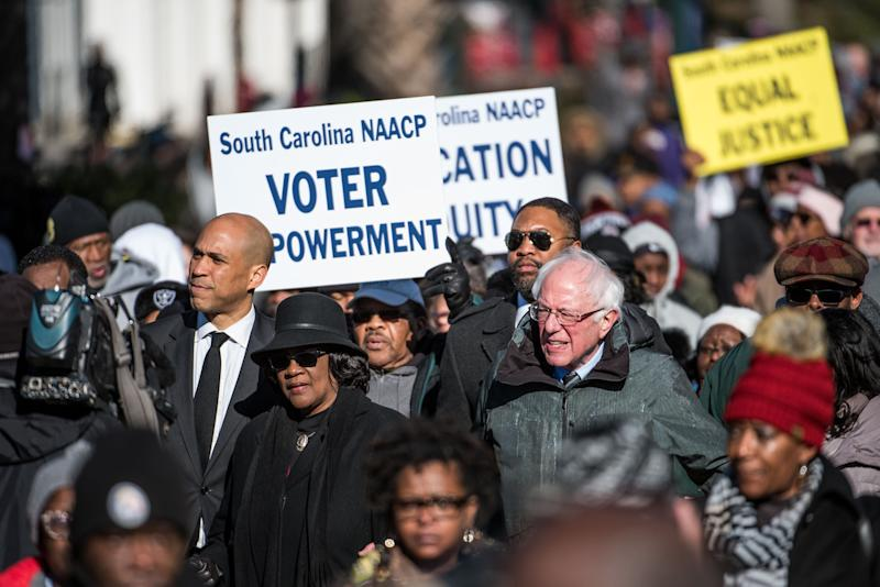 Sen. Bernie Sanders; Brenda Murphy, president of the South Carolina NAACP chapter; and Sen. Cory Booker march down Main Street to the Statehouse in commemoration of Martin Luther King Jr. Day in Columbia, S.C.