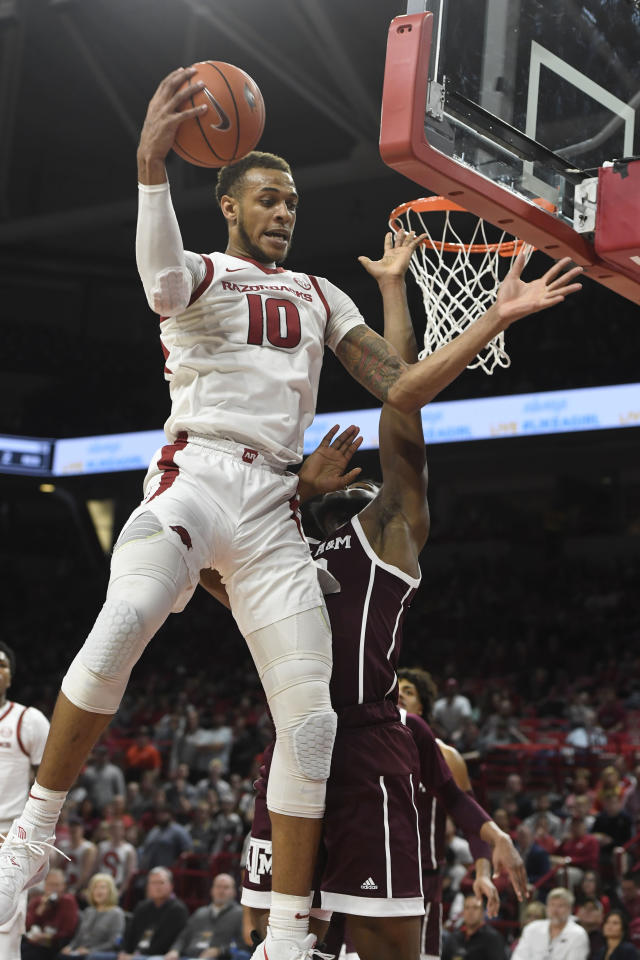Arkansas forward Daniel Gafford (10) pulls in a rebound in front of Texas A&M defender Josh Nebo during the first half an NCAA college basketball game, Saturday, Feb. 23, 2019, in Fayetteville, Ark. (AP Photo/Michael Woods)