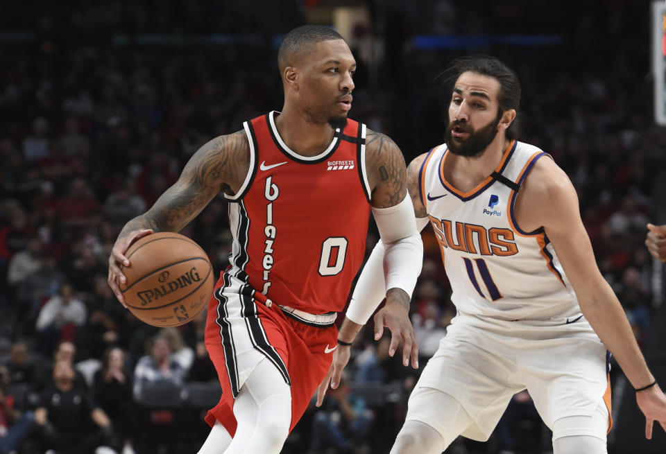 Portland Trail Blazers guard Damian Lillard, left, dribbles the ball past Phoenix Suns guard Ricky Rubio, right, during the first quarter of an NBA basketball game in Portland, Ore., Tuesday, March 10, 2020. (AP Photo/Steve Dykes)