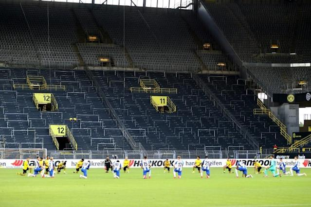 Borussia Dortmund and Hertha berlin players take a knee in solidarity with protests raging across the United States over the death of George Floyd (AFP Photo/Lars BARON)