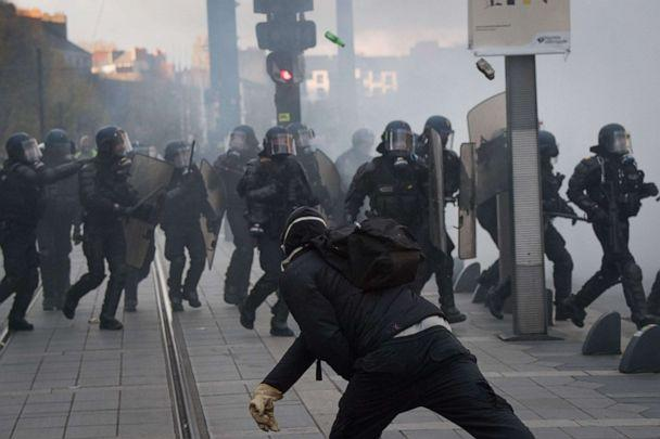 PHOTO: A man throws a stone on CRS anti riot police officers on November 16, 2019, in Nantes, western France during clashes on the sidelines of a demonstration marking the first anniversary of the 'yellow vest' (gilets jaunes) movement. (Loic Venance/AFP via Getty Images)