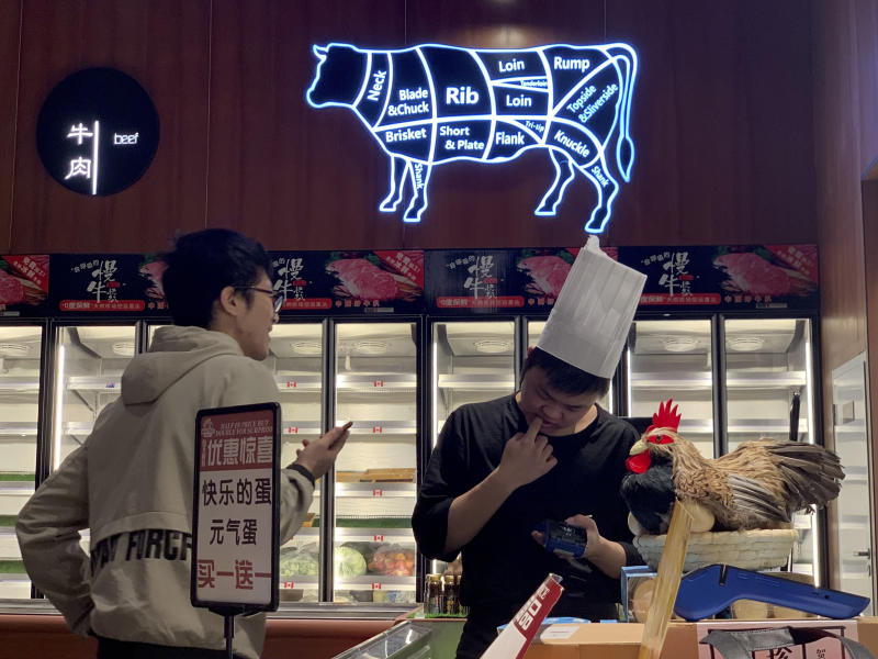 A worker at the imported beef section of a supermarket that used to carry U.S. products chats with another in Beijing on Tuesday, May 14, 2019. China announced higher tariffs Monday on $60 billion worth of American goods in retaliation for President Donald Trump's latest penalties on Chinese products. (AP Photo/Ng Han Guan)