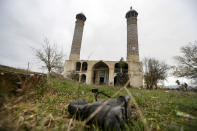 A military boot lies on the grass in front of the Aghdam Mosque in Agdam, prior to the Azerbaijani forces being handed control in the separatist region of Nagorno-Karabakh, Thursday, Nov. 19, 2020. The mosque itself is an especial sore point. In the years after the local population was driven out the mosque was turned into a stable for cattle and swine. Although ethnic Armenian forces tried to keep outsiders away from Aghdam, some camera-bearing visitors slipped in and their photos of the mosque's defilement outraged Azerbaijanis. (AP Photo/Sergei Grits)