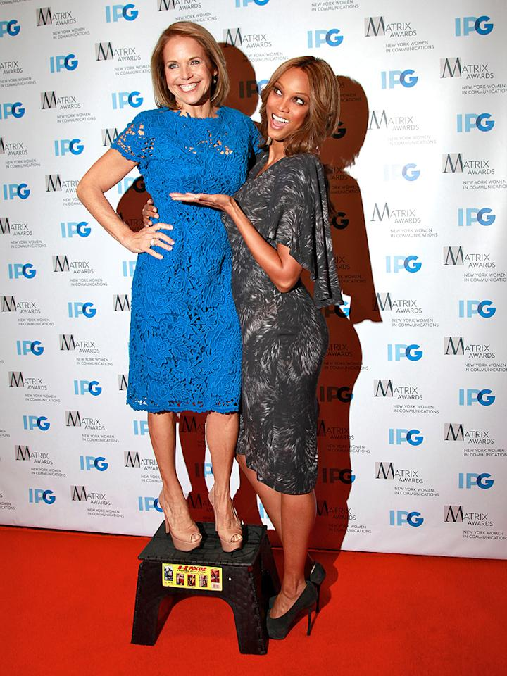 """It's not every day a 5'1"""" woman gets to tower over a supermodel, but Katie Couric got to live the dream (with a little help from a step stool) when she goofed around with Tyra Banks at the 2012 Matrix Awards luncheon. The event, which honors women in communications and the arts, took place at Manhattan's Waldorf Astoria hotel on Monday. (4/23/2012)"""