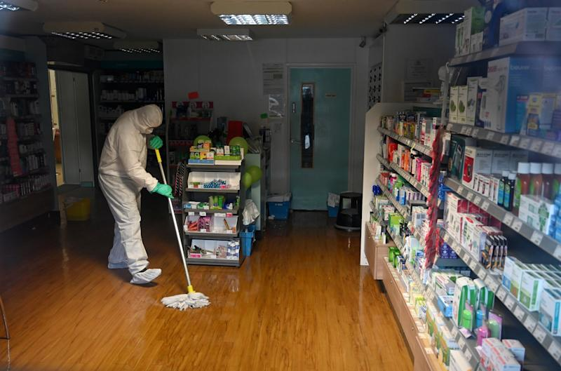 "In this photograph taken through a window, a worker in protective clothing, including face mask and gloves, is pictured cleaning the floor of the pharmacy attached to the at the Warmdene doctor's Surgery at County Oak Medical Centre in Brighton, southern England on February 10, 2020, after it closed for ""urgent operational health and safety reasons"", following reports a member of staff was infected with the 2019-nCoV strain of the novel coronavirus, Covid-19,. - The British government on Monday warned the outbreak of novel coronavirus was a ""serious and imminent threat"" and reported four new cases that brought the total recorded in the country to eight. Two hospitals The Royal Free and Guys and St Thomas', have both been designated as ""isolation"" facilities, with both currently housing Britons who have returned from Wuhan, the Chinese city at the centre of the outbreak. (Photo by Glyn KIRK / AFP) (Photo by GLYN KIRK/AFP via Getty Images)"